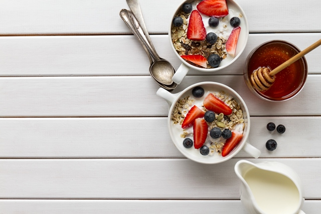 Tasty colorful Breakfast with Oatmeal, Yogurt, Strawberry, Blueberry, Honey and Milk on White Wooden Background with Copy Space. Top View.